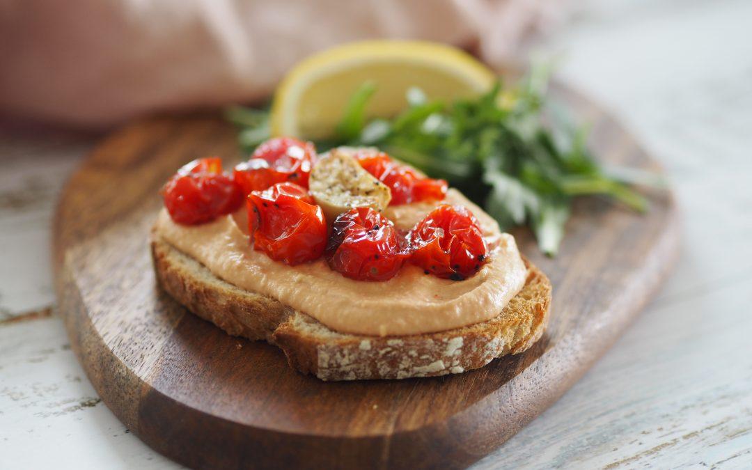Deilig brødskive med hummus og bakte tomater